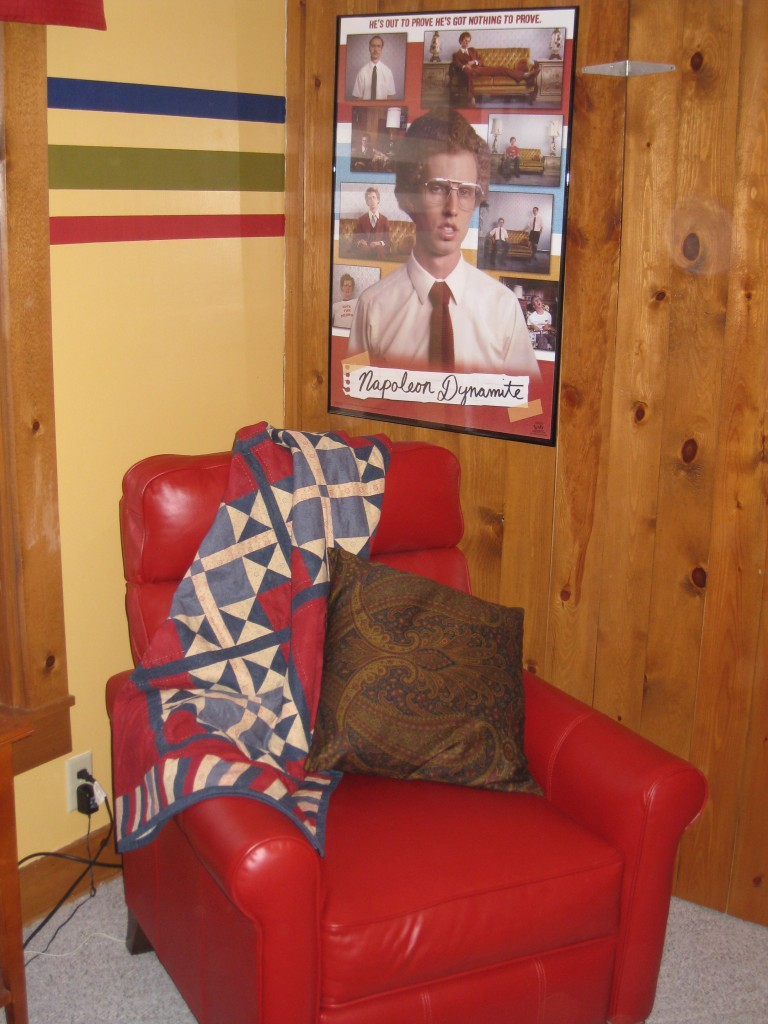 The red chair, a quiulted throw and another movie poster make this corner very cozy.