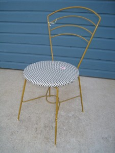 A cut little bistro style chair in it's original yellow paint and vinyl seat