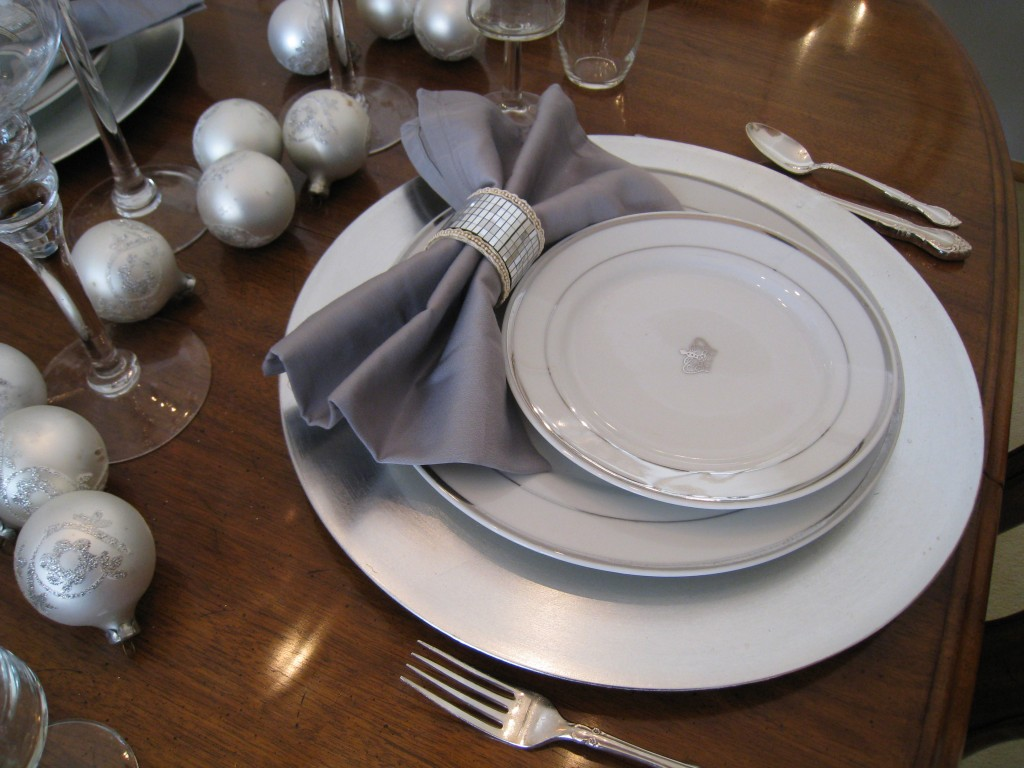 Traditionally, the charger or dinner plate should be within an inch from the edge of the table.  There aren't any rules about where to place the salad plate!
