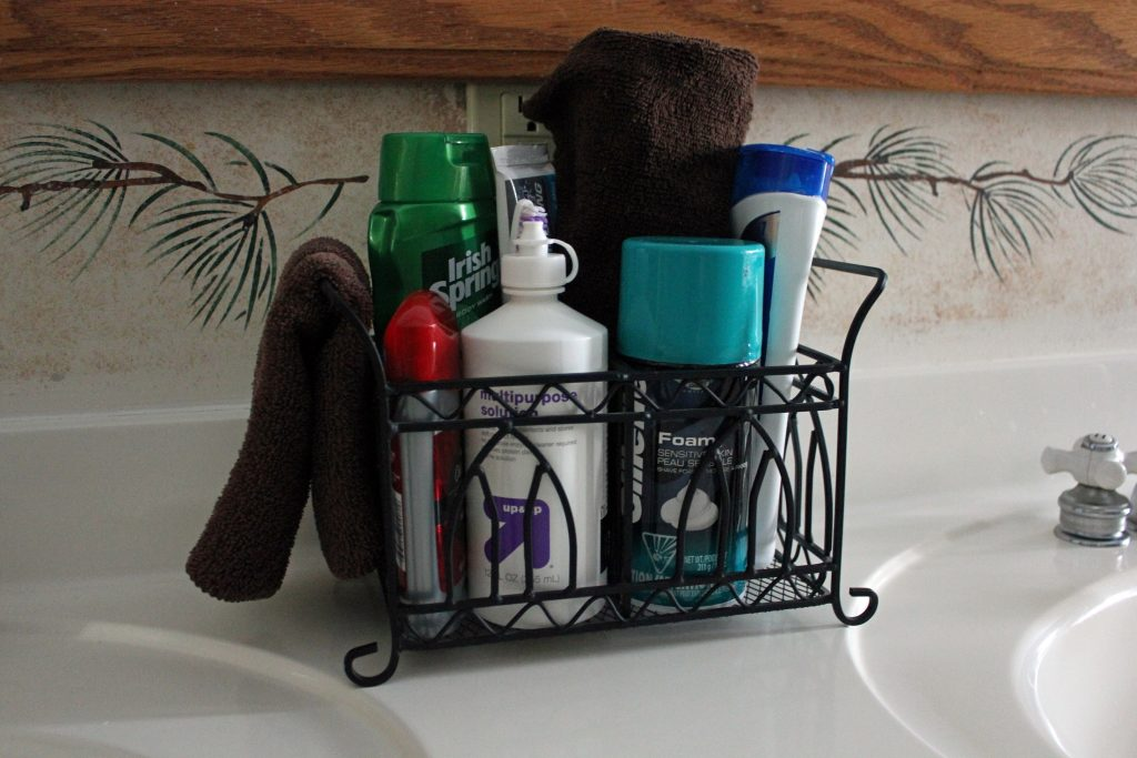 A kitchen utensil basket holds lots of toiletries.